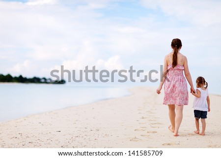 Mother and her little daughter on tropical beach vacation - stock photo