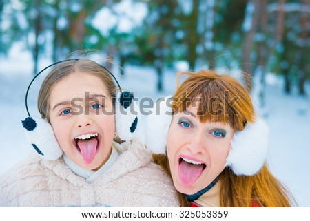 mother and her little daughter outdoors on beautiful winter day. girls in winter forest. Two girls having fun in winter, winter fun outdoors. surprise winter discounts. funny portrait in winter  - stock photo