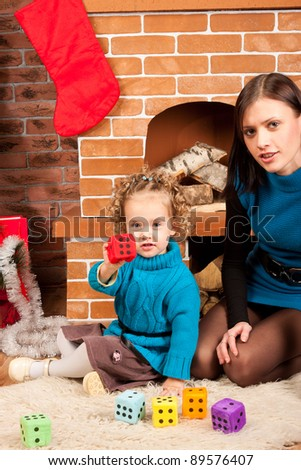 Mother and her  little daughter playing near Christmas tree - stock photo
