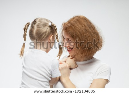 Mother and her little daughter playing, neutral background - stock photo