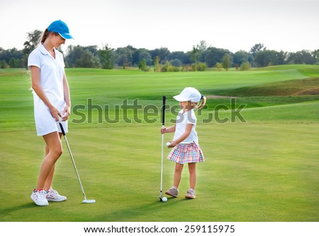 Mother and her little daughter practicing to hit the ball at the course - stock photo