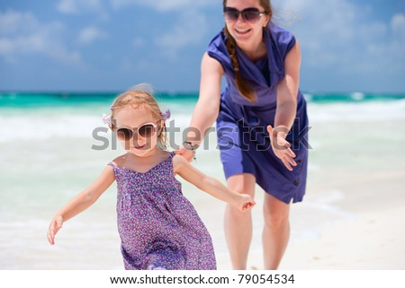 Mother and her little daughter running at tropical beach - stock photo