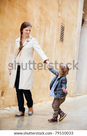 Mother and her little daughter walking in city - stock photo