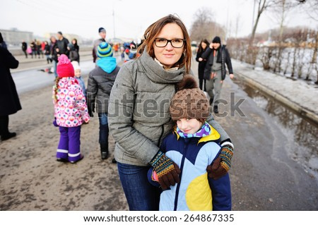 Mother and her little daughter walking in city on cold weather - stock photo