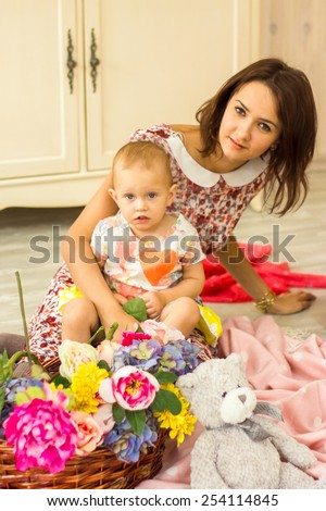 Mother and her little daughter with basket of flowers - stock photo