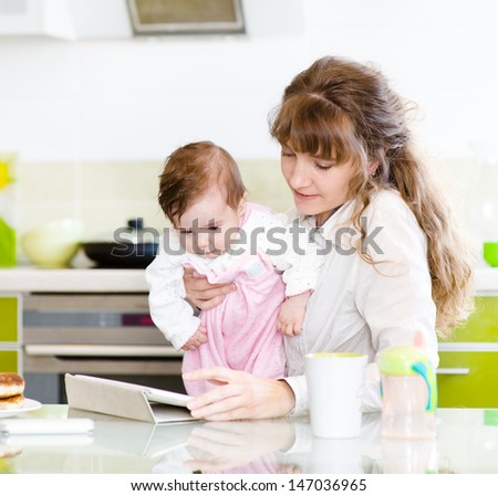 mother and her little daughter with tablet pc