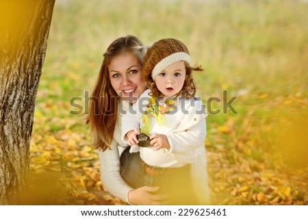 mother and her little girl in fall - stock photo