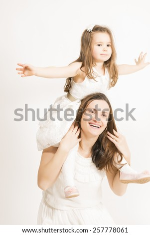 Mother and her little lovely daughter, concept of togetherness, studio shot. Mother and daughter having fun playing - stock photo