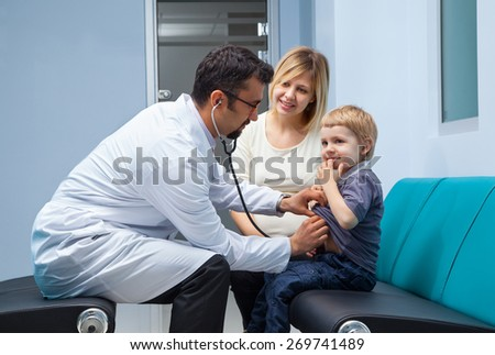mother and her little son checked by a doctor at the hospital  - stock photo