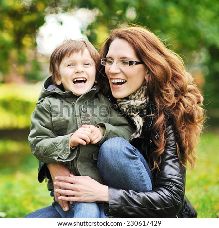 Mother and her little son having fun in a park - stock photo