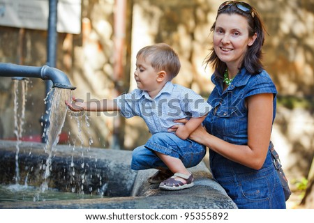 Mother and her little son outdoors in city near fountain - stock photo
