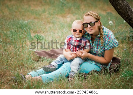 Mother and her little son posing in a green garden