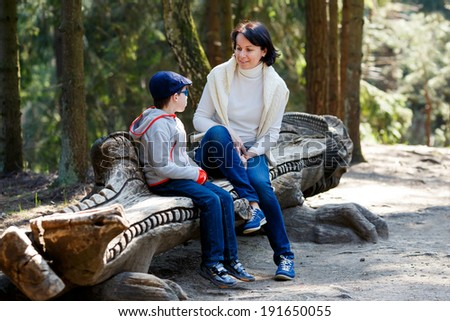 Mother and her little son sitting on a bench - stock photo