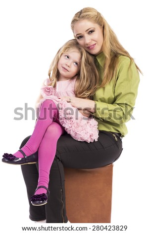 Mother and her lovely daughter sitting and looking at camera  over white background - stock photo