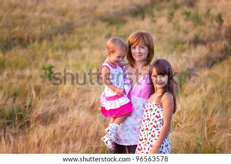 Mother and her lovely two daughter in wheat field - stock photo