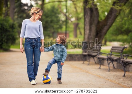 Mother and her playful little son walking in a park - stock photo