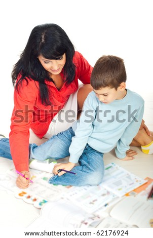 Mother and her preschool son sitting on floor in house and drawing papers ,reading books and teaching him - stock photo