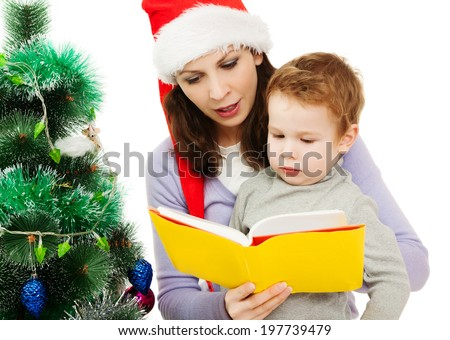 Mother and her small boy in Santa hat reading book
