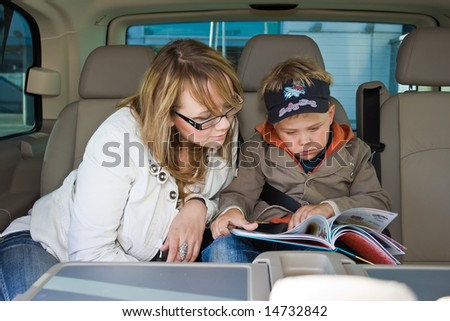 mother and her son are reading a book on a backseat of a car - stock photo
