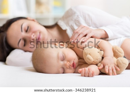 mother and her son baby sleeping together in a bedroom - stock photo