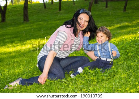 Mother and her son having fun in grass and the toddler waving hand - stock photo