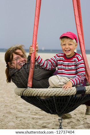 Mother and her son in beach playground. Windy summer day. - stock photo