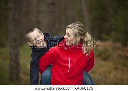 Mother and her son in the forest - stock photo