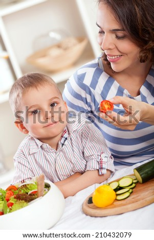 Mother and her son is eating salad - stock photo