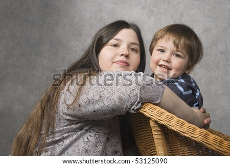 Mother and her son look at camera smiling - stock photo