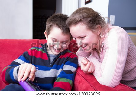 Mother and her son looking at the tablet. He is showing his creativity happily while she is showing her interest. - stock photo