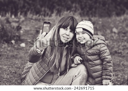mother and her son outdoors making selfie - stock photo