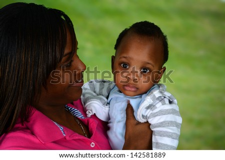 Mother and her son playing outside together - stock photo