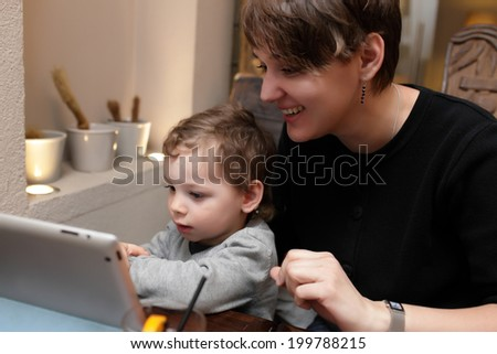 Mother and her son playing with tablet PC - stock photo