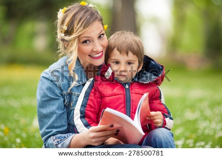 Mother and her son reading a book while having a picnic in nature