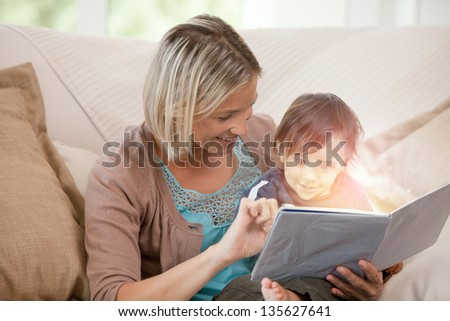 Mother and her son reading a glowing story together on the couch at home - stock photo