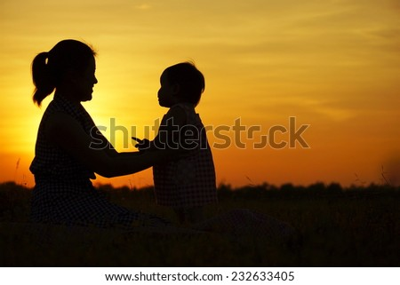 mother and her son silhouette - stock photo