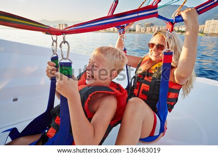 Mother and her son sit in moving motorboat and ready to soar and paraglide, focus on mother - stock photo