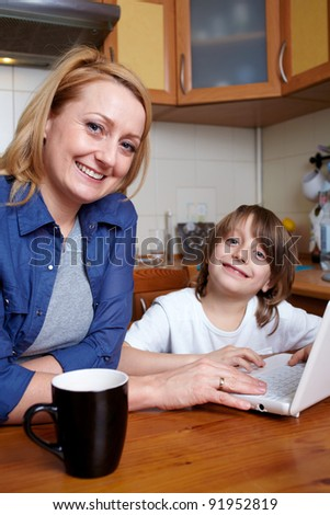 Mother and her son sits at kitchen table and play with small laptop