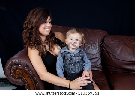 Mother and her son sitting on a couch with eye contact and smiles