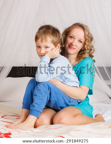 Mother and her son sitting on big bed in bedroom