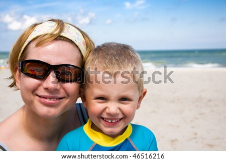 Mother and her son smiling on beach in summer day - stock photo