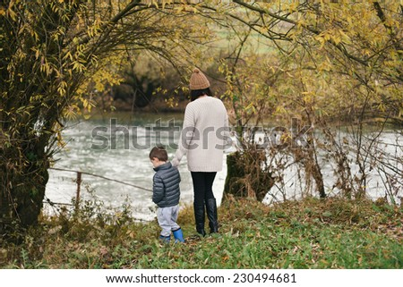 Mother and her son standing by the river in autumn  - stock photo
