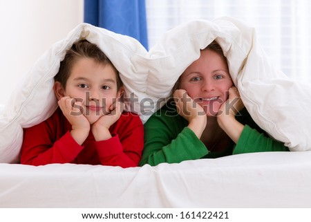 Mother and her son under the blanket with Christmas color pajamas, smiling to you - stock photo