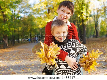 Mother and her son walking in a autumn park