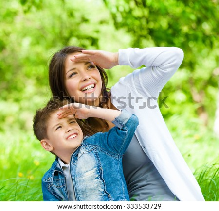 Mother and her son with book sitting on green grass cover eyes from sun in park. Concept of happy family relations and carefree leisure time - stock photo