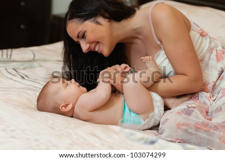 Mother and  her sweet  baby in the room at home. Happy family. - stock photo