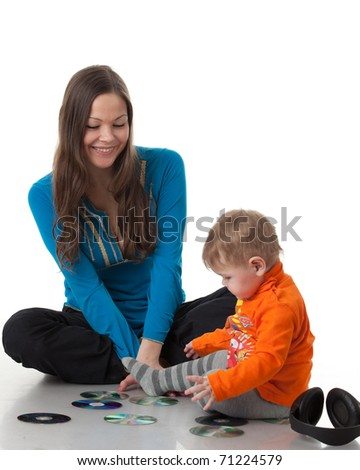 Mother and  her sweet  baby  with earphones and CD  on a white background. Happy family. - stock photo