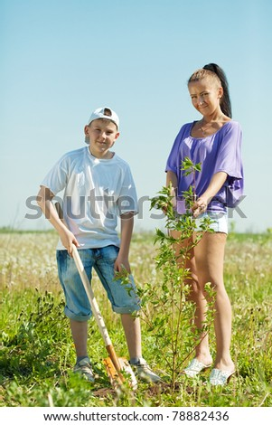Mother and her teen boy planting tree - stock photo