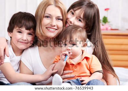 Mother and her three offspring in the bedroom - stock photo
