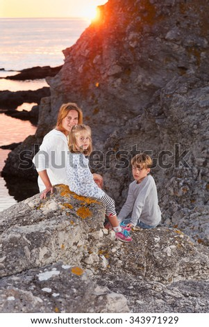 Mother and her two children, a boy and a girl sitting on a rock at the seashore and enjoying the sunset. Island Faroe, Sweden. - stock photo
